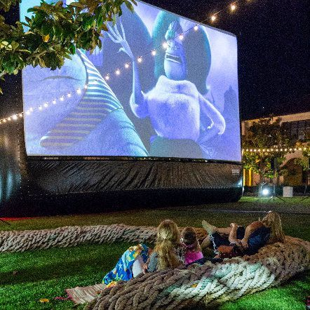 Girls sitting on ground watching a backyard screen rental