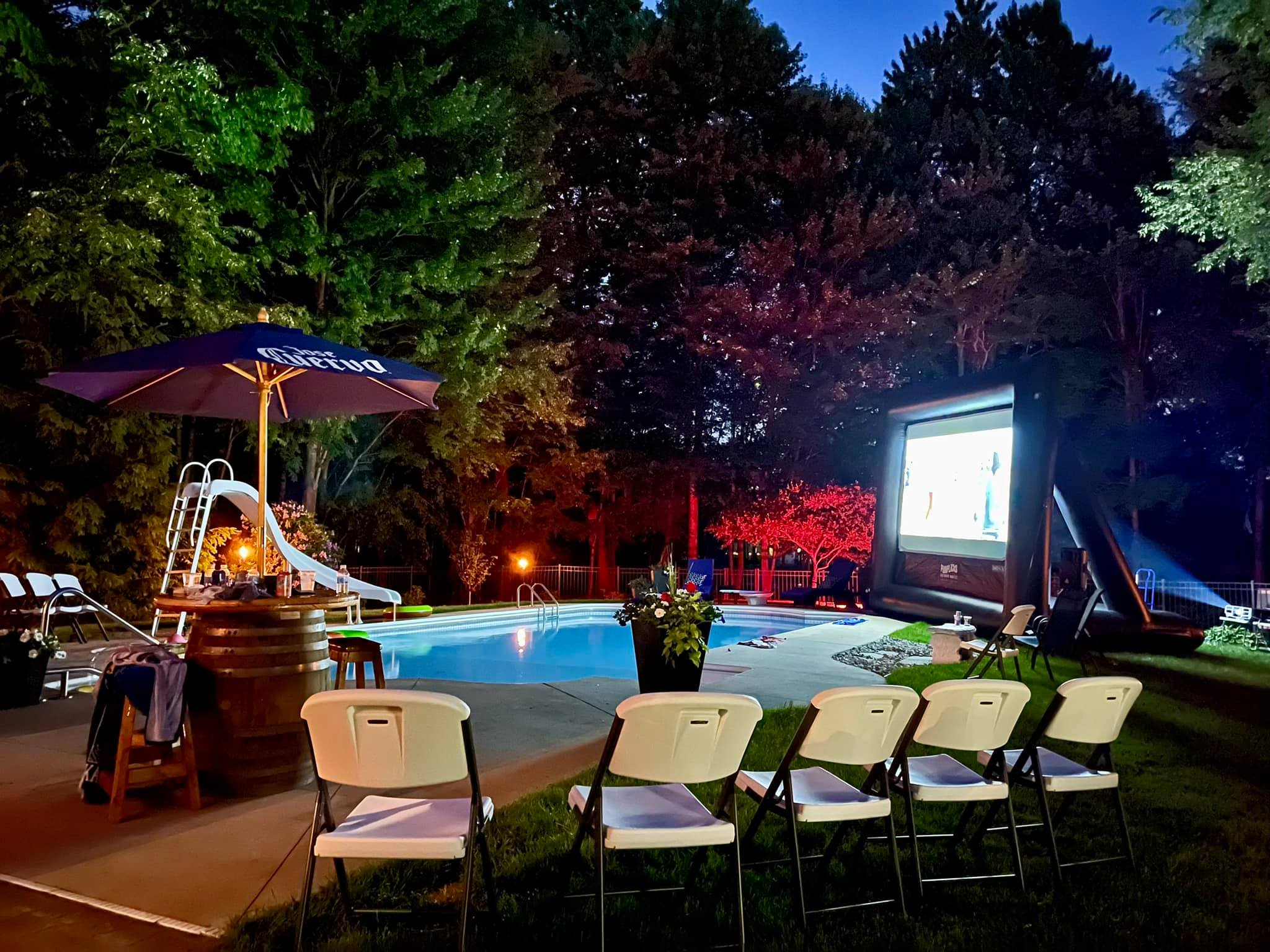 Backyard pool party theme including a movie screen next to the swimming pool