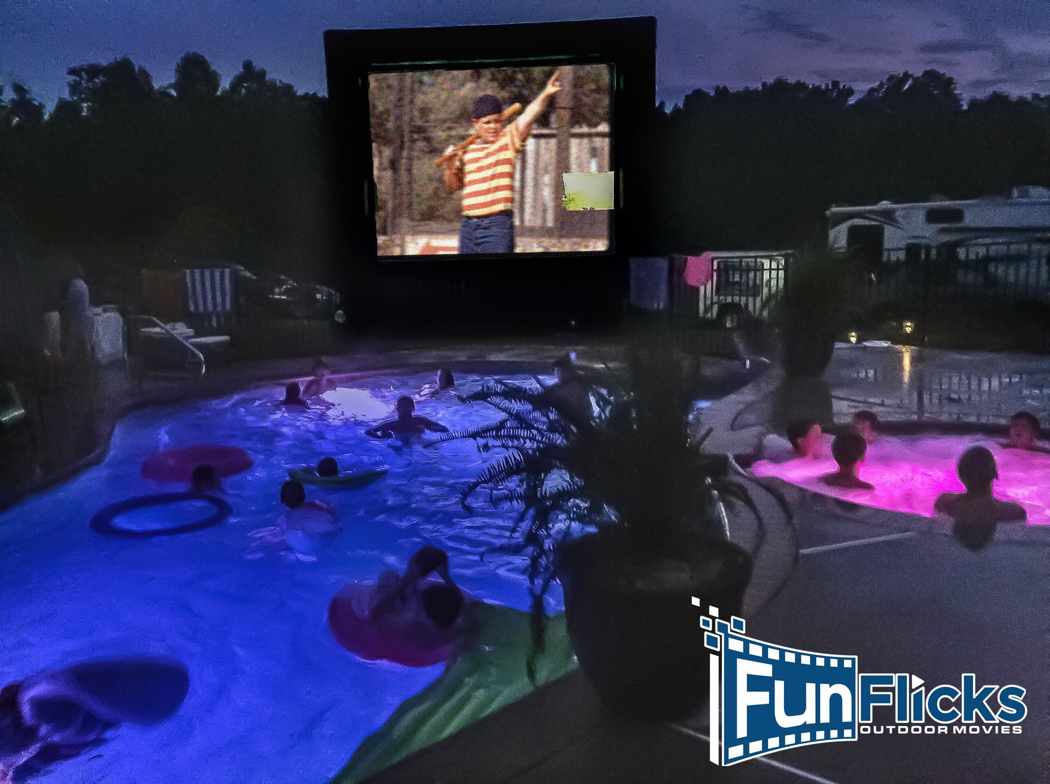 Night pool party ideas include a screen placed on your pool deck for an outdoor movie